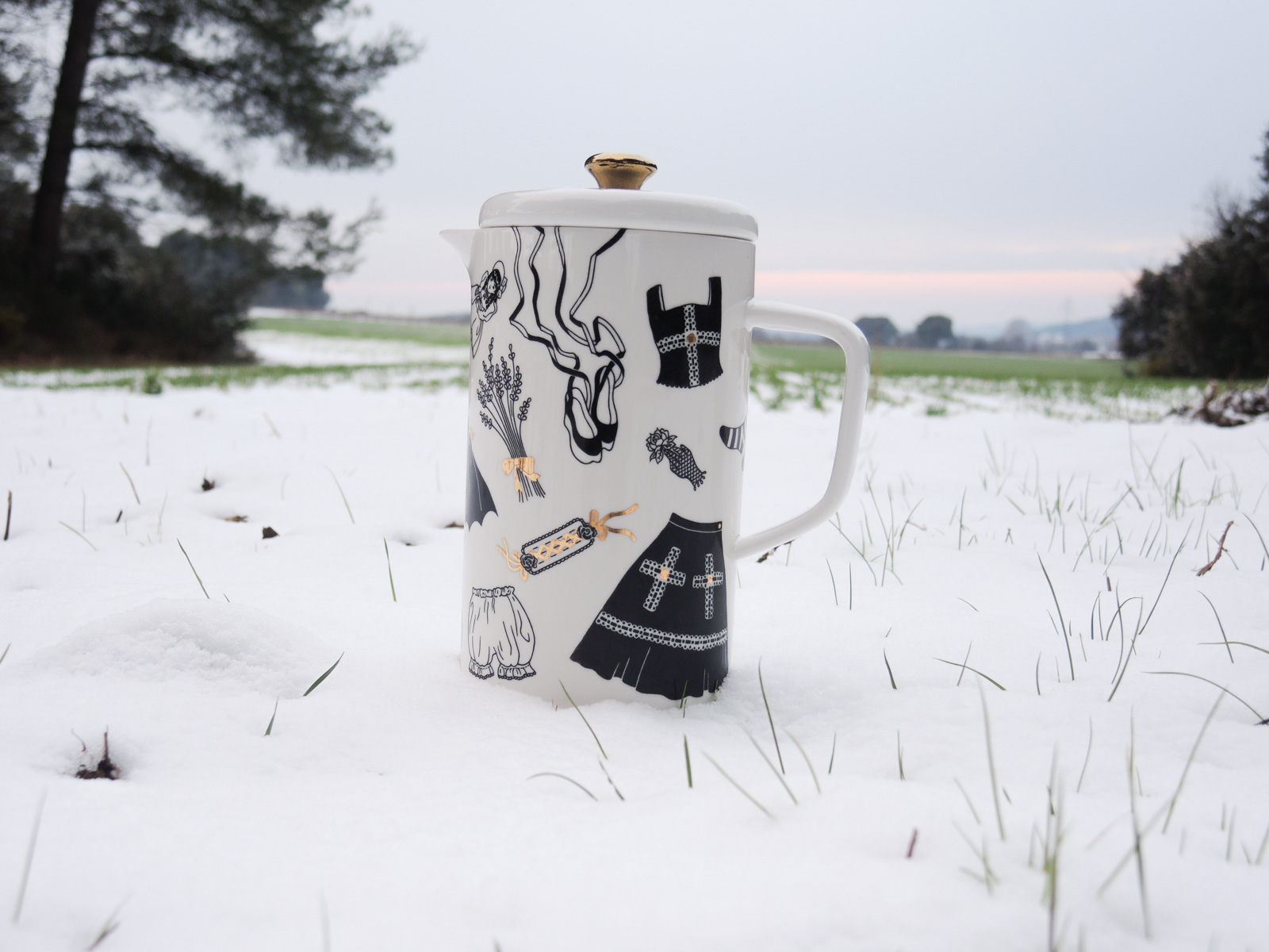 """Black coffee pot - 3rd one - from """"Oldschool Lolita"""", a collection of painted porcelains by messalyn, standing in the snow in a field at sunset"""