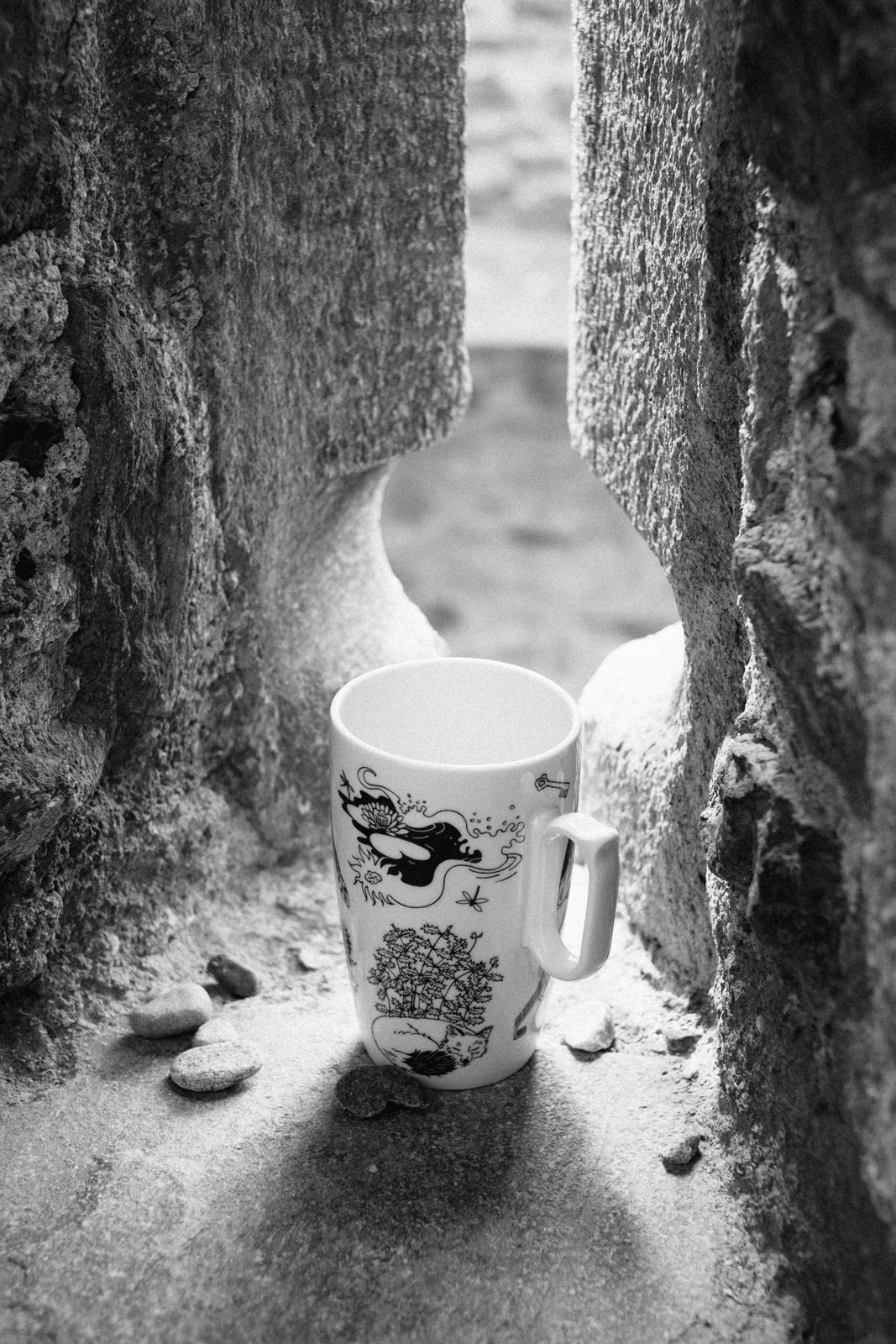 "Black and white photograph of a purple mug from ""Enchanteresse"", a collection of painted porcelains by messalyn, standing on a windowsill in the italian castle of Fénis"