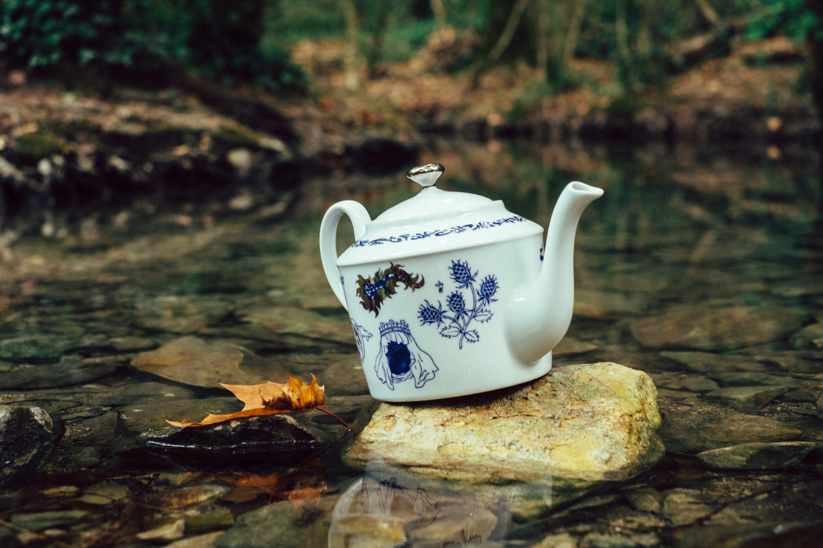"Blue teapot from ""Enchanteresse"", a collection of painted porcelains by messalyn, standing on a rock in a small pool in the forest"